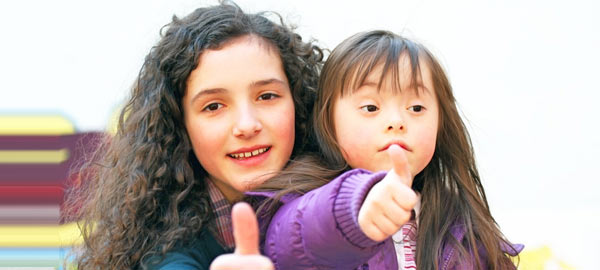 Two girls smiling with thumbs up, one with intellectual disability